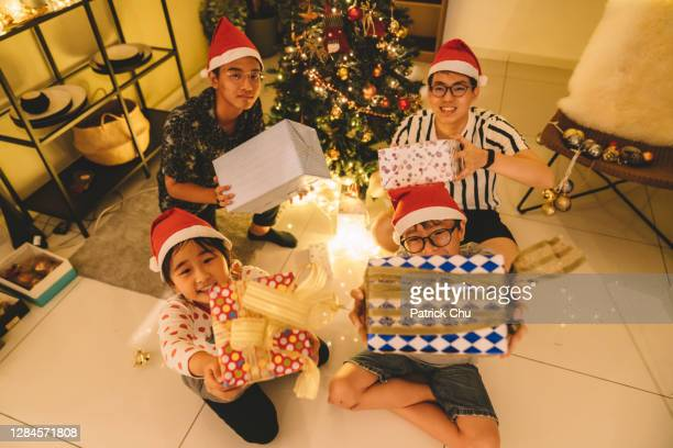 asian chinese friends and siblings holding presents looking at camera during christmas celebration - 12 17 months stock pictures, royalty-free photos & images