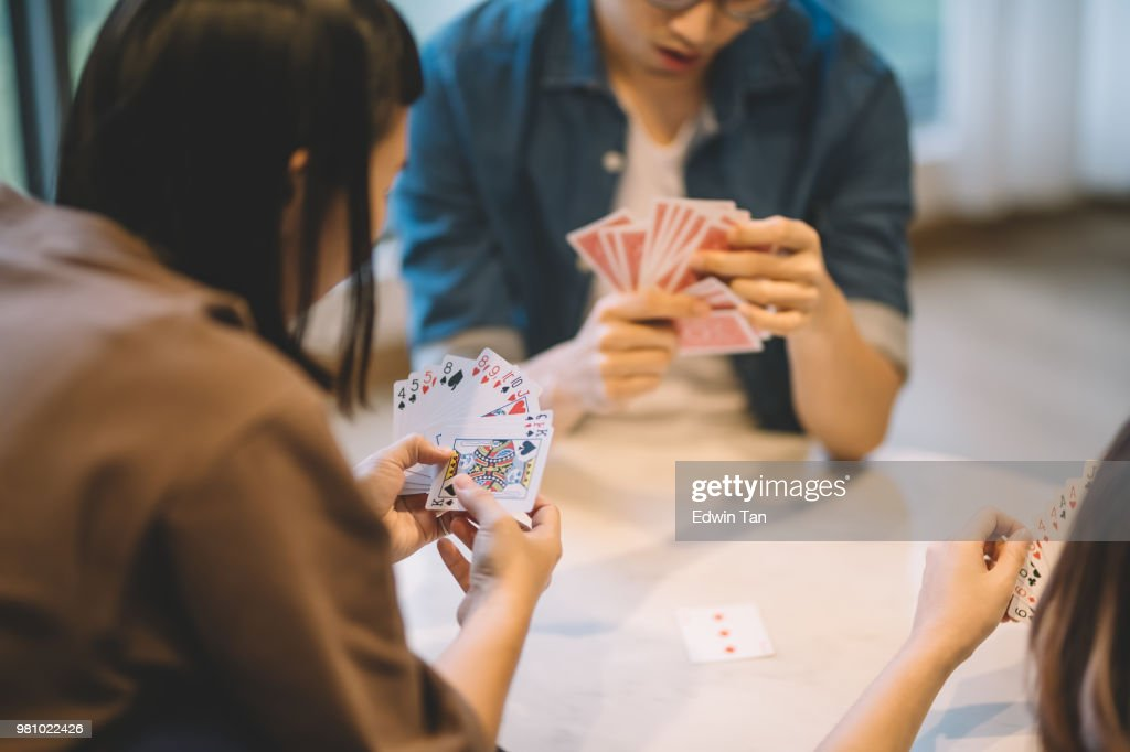 asian chinese friends playing poker cards game in living room : Stock Photo