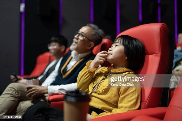 asian chinese grandfather with his grandchildren at movies theater eating popcorn and watching a film - film industry stock pictures, royalty-free photos & images