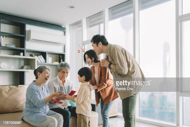 asian chinese grandparents giving out red packets angpao to grandson during chinese new year at home - patrick grant stock pictures, royalty-free photos & images