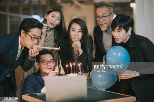 asian chinese group of coworker looking at laptop video conference celebrating birthday wit their colleague - hot desking stock pictures, royalty-free photos & images