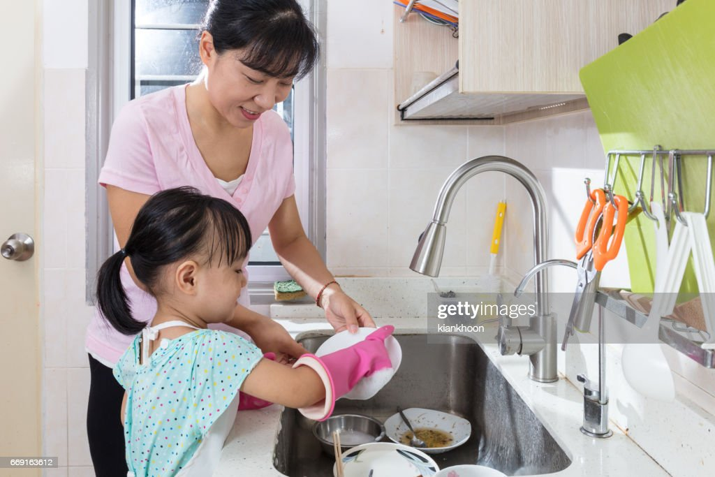 Asian Chinese little girl helping mother washing dishes : Stock Photo