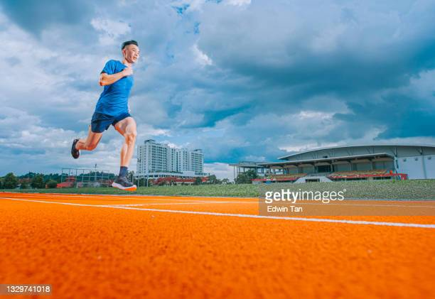 asian chinese male athletes running at track cloudy late evening in track and field stadium - try scoring stock pictures, royalty-free photos & images