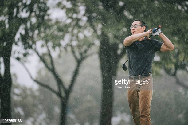 asian chinese male golfer playing golf in the rain in melaka alone wet