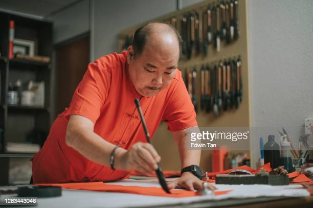 asian chinese male practising chinese caligraphy for coming chinese new year celebration home decoration purpose with prosperity and good wording by writing it on a red piece of paper
