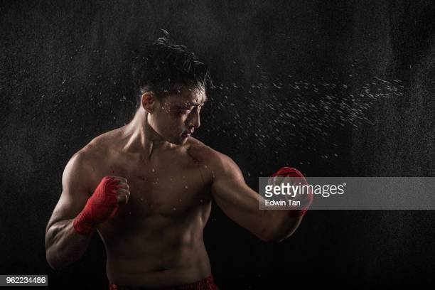 asian chinese male with boxing outfit in raindrops and sweat - asian six pack stock photos and pictures