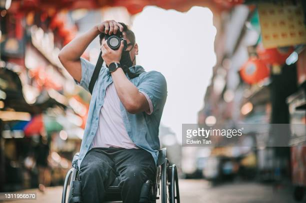 asian chinese male with physical disability on wheelchair photographing in china town sitting on his wheelchair - photojournalist stock pictures, royalty-free photos & images
