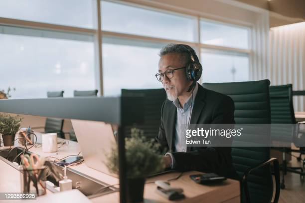 asian chinese mature businessman with beard typing and replying email to his customer and video call with his client in the office using laptop - chinese ethnicity stock pictures, royalty-free photos & images