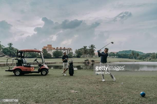 アジアの中国の成熟した男ゴルファーは、彼の息子が観察している間、ゴルフコースでティーオフする準備をしています - ティーショット ストックフォトと画像