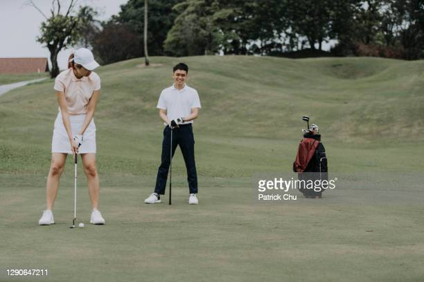 asian chinese mature woman golfer preparing to putt golf ball while her friend is observing at golf course - friendly match stock pictures, royalty-free photos & images