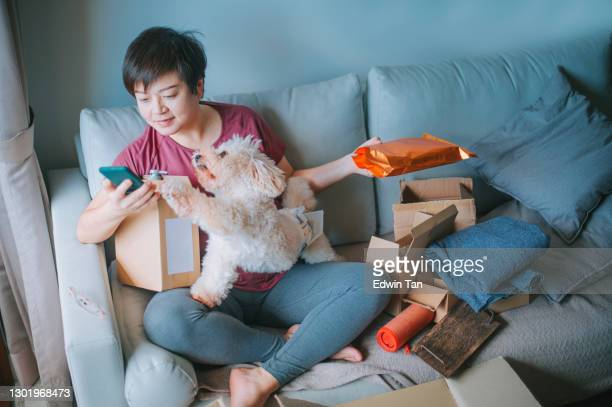 asian chinese mid adult woman happily unpacking opening all packages received all her parcel from online shopping with all her purchased delivered in living room sofa - unboxing stock pictures, royalty-free photos & images