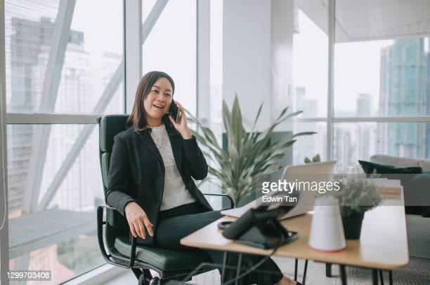 asian chinese mid adult woman white collar worker working in her office room listening to her phone - chairperson stock pictures, royalty-free photos & images