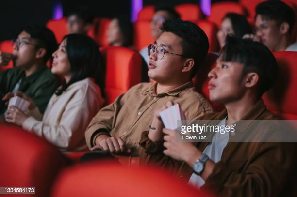 asian chinese mixed age group audience watching movie sitting in a row in cinema movie theater enjoying - film premiere stock pictures, royalty-free photos & images