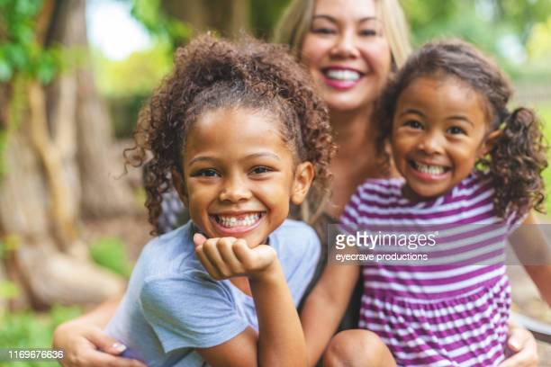 asian chinese mother with two daughters of mixed chinese and african american ethnicity in a green lush back yard setting posing for portraits smiling and being silly - adoption stock pictures, royalty-free photos & images