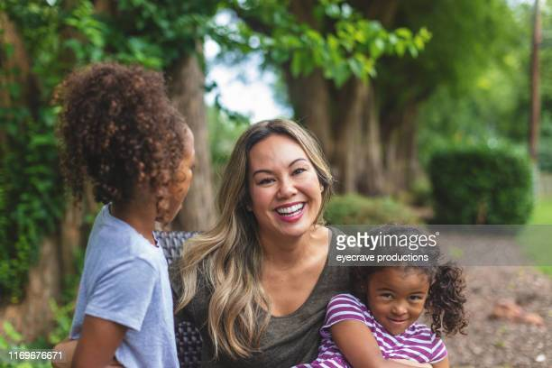 Asian Chinese Mother with two daughters of mixed Chinese and African American ethnicity in a green lush back yard setting posing for portraits smiling and being silly