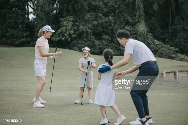 asian chinese parent golfer teaching daughter playing golf at golf course weekend - golf stock pictures, royalty-free photos & images
