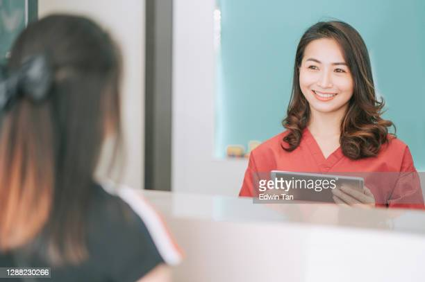 asian chinese patient registering at dentist office reception - medical receptionist uniforms stock pictures, royalty-free photos & images