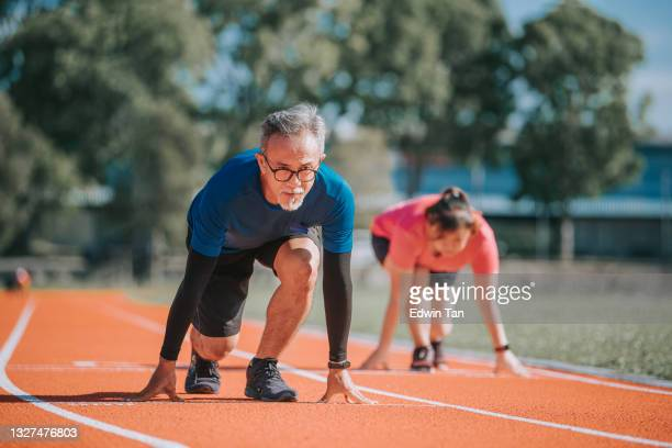asian chinese senior couple getting ready to sprint at track and field stadium in the morning - forward athlete stock pictures, royalty-free photos & images