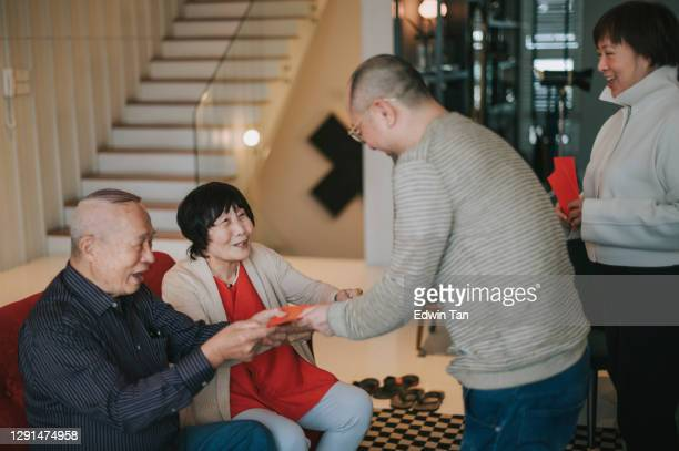 asian chinese senior couple receiving red envelop angpao red packet from their children adult offspring chinese new year - chinese new year stock pictures, royalty-free photos & images