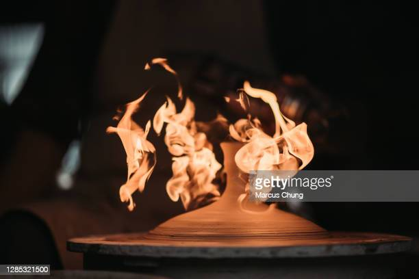 asian chinese senior man clay artist making pottery with blow torch in his craft studio - artist stock pictures, royalty-free photos & images