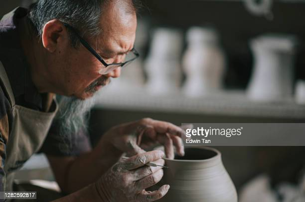 asian chinese senior man clay artist working in his studio with spinning pottery wheel - art and craft product stock pictures, royalty-free photos & images