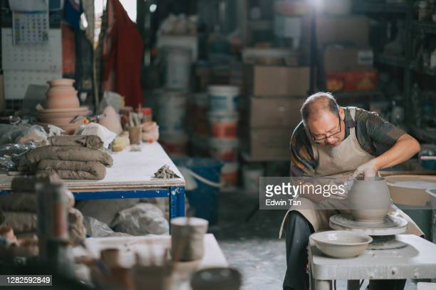 asian chinese senior man clay artist working in his studio with spinning pottery wheel - craftsperson stock pictures, royalty-free photos & images