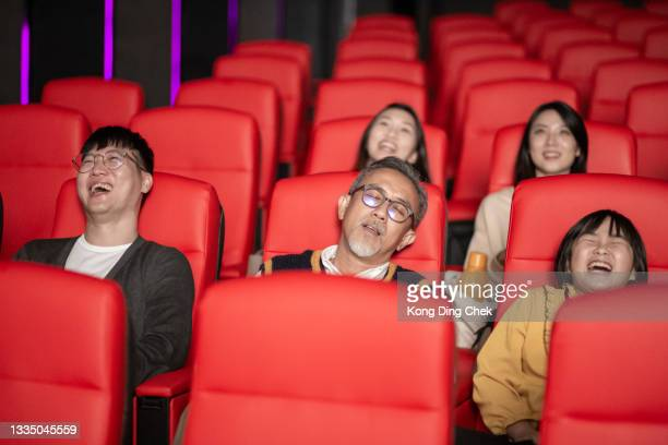 asian chinese senior man fall asleep watching movie with his grandchildren in the cinema movie theater exhaustion - film premiere stock pictures, royalty-free photos & images