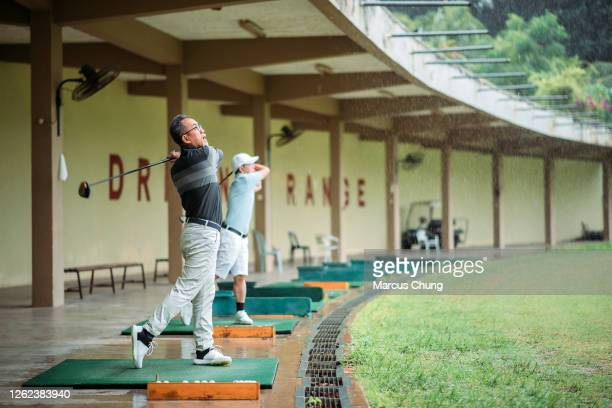 asian chinese senior man golfer teeing off and swing his golf club at golf driving range - driving range stock pictures, royalty-free photos & images