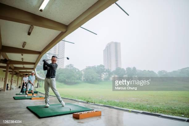 アジアの中国のシニアマンゴルファーは、ゴルフのドライビングレンジで彼のゴルフクラブをティーオフし、スイング - ゴルフ練習場 ストックフォトと画像