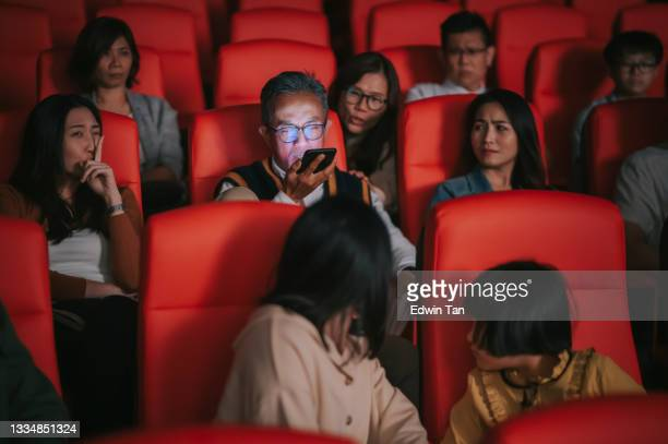asian chinese senior man talking over the phone loudly  during cinema movie show time in the dark disturbing and ignoring other audience around him - film premiere stock pictures, royalty-free photos & images