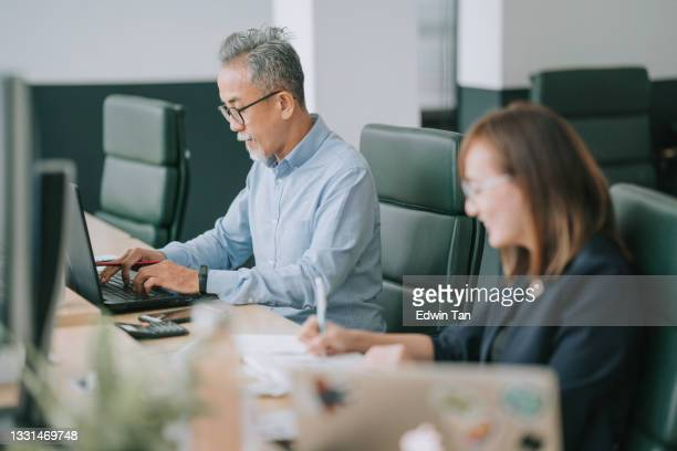 オフィスオープンプランで働くラップトップタイピングを使用して顔の毛を持つアジアの中国のシニア男性 - ワーキングシニア ストックフォトと画像