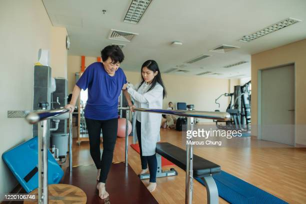 asian chinese senior women holding parallel bars and walking while physical therapists helping at side in a rehab centre at hospital - railings stock pictures, royalty-free photos & images