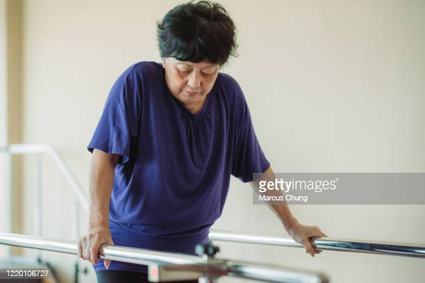 asian chinese senior women practicing, holding parallel bars and walking in a rehab centre at hospitalasian chinese senior women holding parallel bars and walking in a rehab centre at hospital - railings stock pictures, royalty-free photos & images