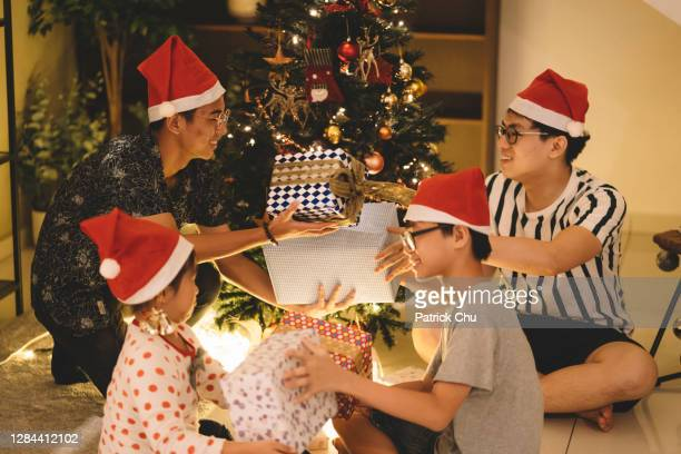 asian chinese siblings and friends exchanging presents during christmas celebration - patrick grant stock pictures, royalty-free photos & images