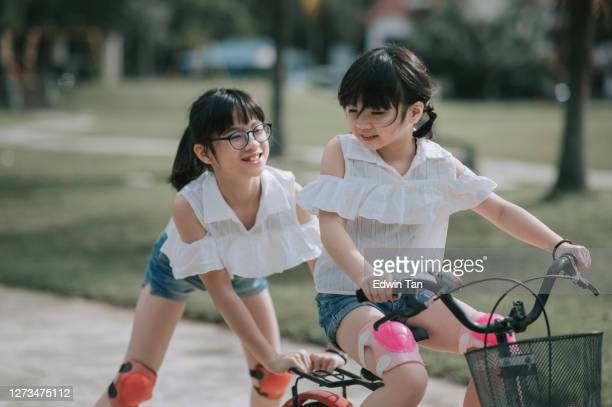 asian chinese sister pushing and helping her sister learning riding bicycle at public park in weekend morning - doing a favor stock pictures, royalty-free photos & images