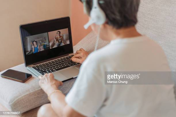 asian chinese smiling senior woman sitting on sofa using laptop with headset at home - three people stock pictures, royalty-free photos & images