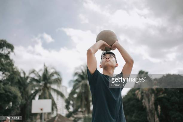 asian chinese teenage boy getting ready to score and practicing at basketball court in weekend morning - try scoring stock pictures, royalty-free photos & images
