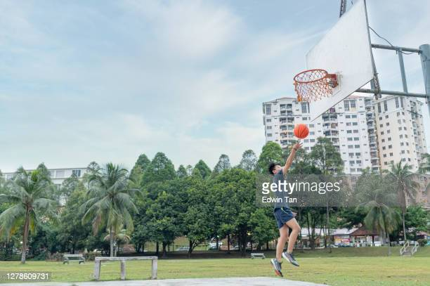 asian chinese teenage boy playing basket ball during weekend - try scoring stock pictures, royalty-free photos & images