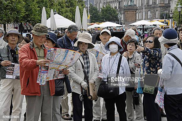 COPENHAGEN /DENMARK Asian chinese tourists one with mask tourist guaide and city may at amager torv stroeget 28 JUNE 2014