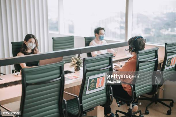 asian chinese white collar worker back to work after quarantine with new sop and social distancing illness prevention safety precautions - new normal stock pictures, royalty-free photos & images