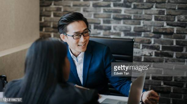 2 asian chinese white collar workers having discussion  using laptop - financial occupation stock pictures, royalty-free photos & images