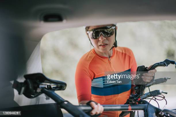 asian chinese woman professional cyclist taking down her bicycle from the suv car trunk ready to cycle - forward athlete stock pictures, royalty-free photos & images