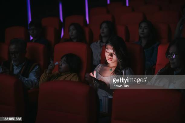 asian chinese woman reading phone message during cinema movie show time in the dark ignoring ansd disturbing other audience around her - film premiere stock pictures, royalty-free photos & images