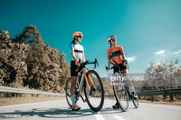 asian chinese woman road bike cyclist leaning on road divider resting - road cycling stock pictures, royalty-free photos & images