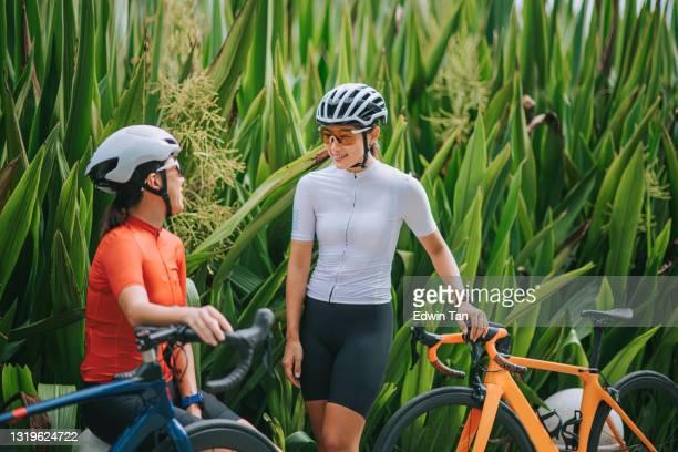 2 aziatische chinese fietsfietser van de vrouwenfietser zij aan zij bij openbaar park in de ochtend rustend het spreken - wielrennen stockfoto's en -beelden
