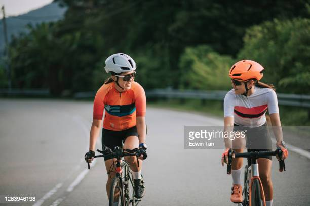 2 asian chinese woman road cyclist cycling in rural area in the morning - forward athlete stock pictures, royalty-free photos & images