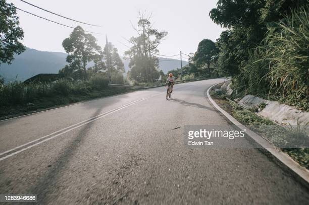 asian chinese woman road cyclist cycling in rural area in the morning - forward athlete stock pictures, royalty-free photos & images