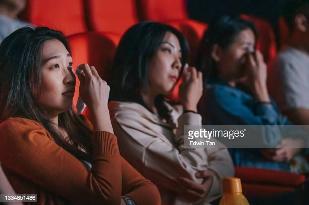 asian chinese women crying watching sad sentimental  drama movie in cinema movie theater wiping teardrop with tissue paper. - film premiere stock pictures, royalty-free photos & images