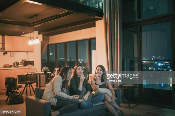 3 asian chinese women having friday night gathering at apartment with tv movie night enjoying snack sitting on sofa enjoying each company - party social event stock pictures, royalty-free photos & images