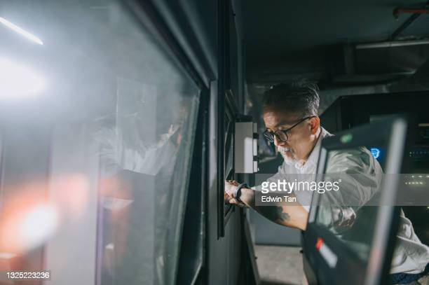 asian chinese working senior man movie operator looking at smart watch checking the time  from movie projection room backstage observing watching movie playing - film premiere stock pictures, royalty-free photos & images
